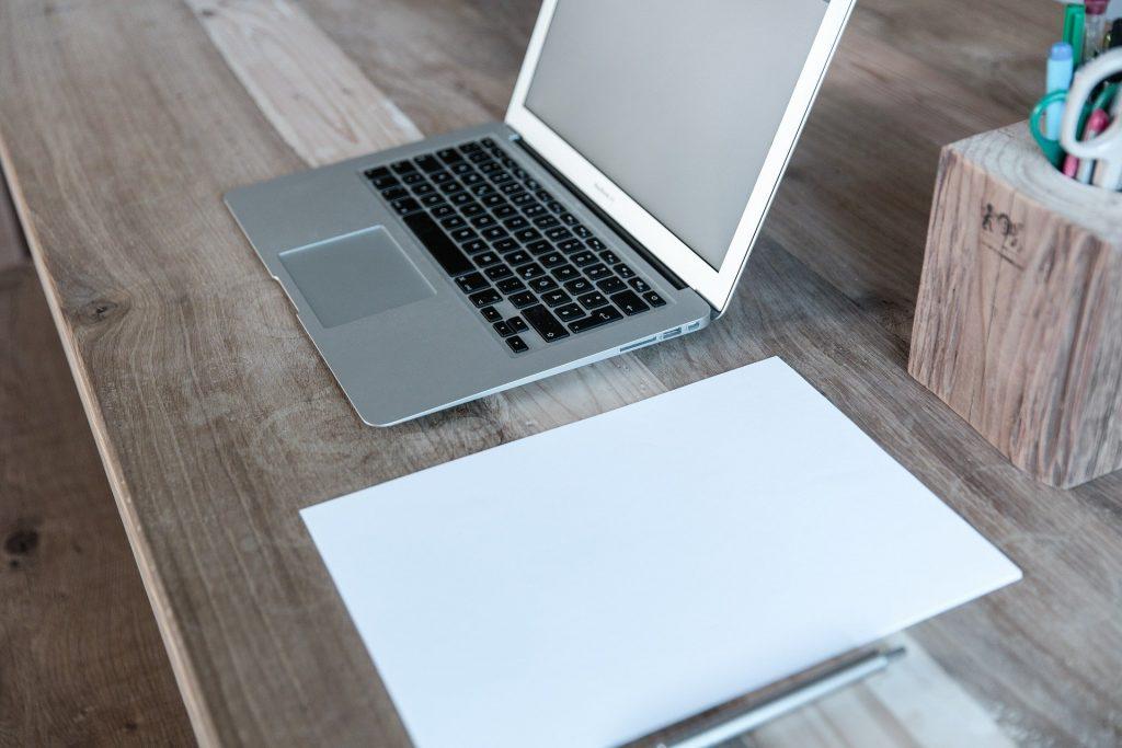Un ordenador y un folio en una mesa de madera para buscar cómo hacer un presupuesto