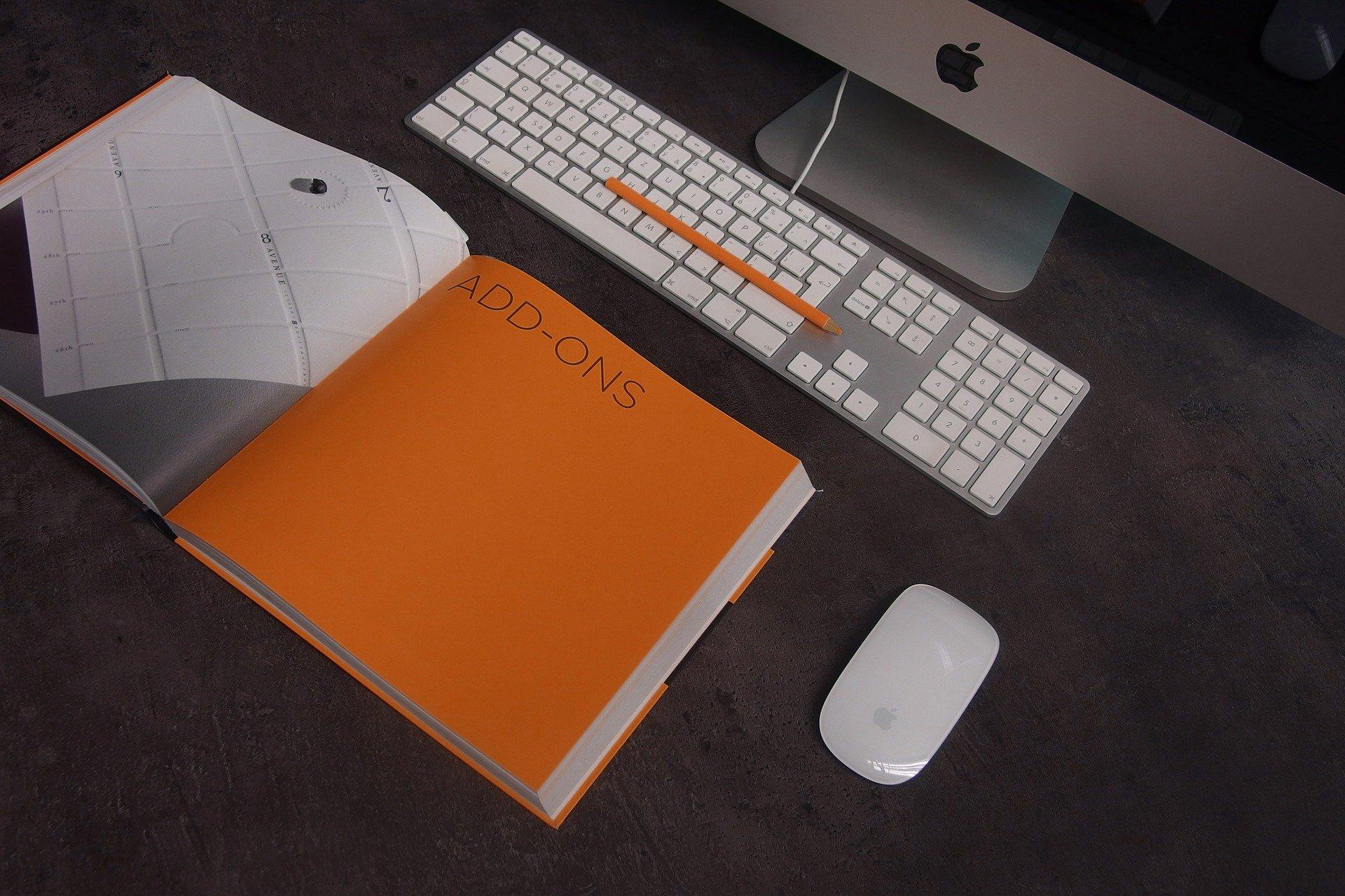 Una libreta naranja y un ordenador para investigar sobre el seguro de responsabilidad civil