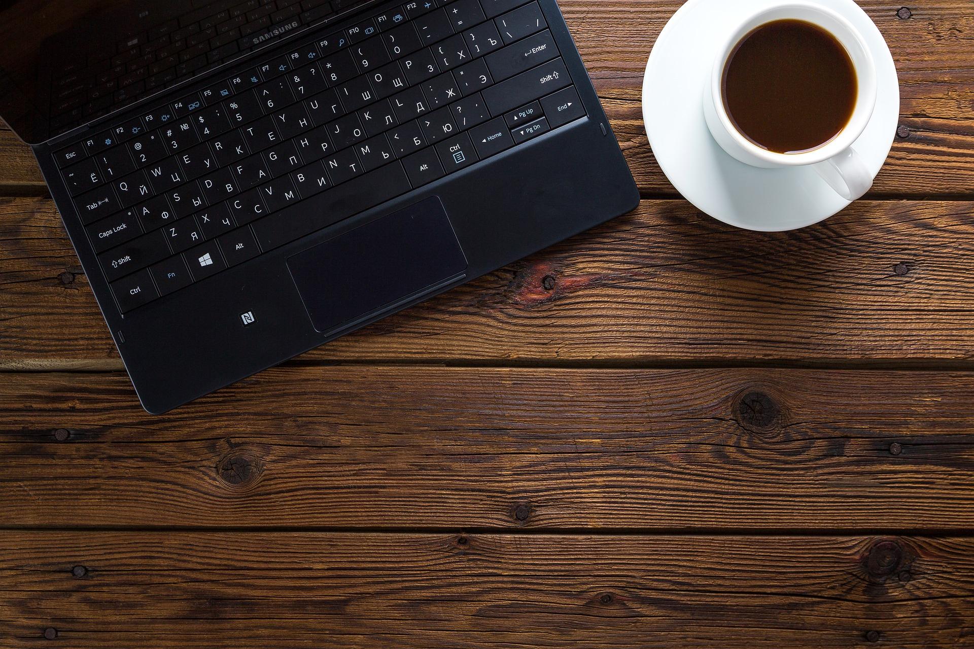 Un ordenador y una taza de café para elegir la mejor gestoría online