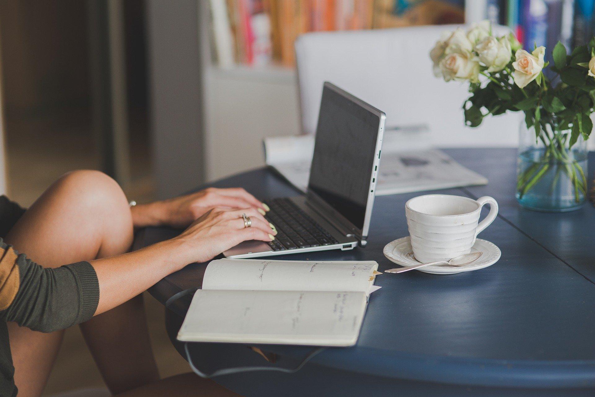 Los brazos de una chica buscando en un ordenador información sobre el autónomo societario con una taza y una libreta al lado