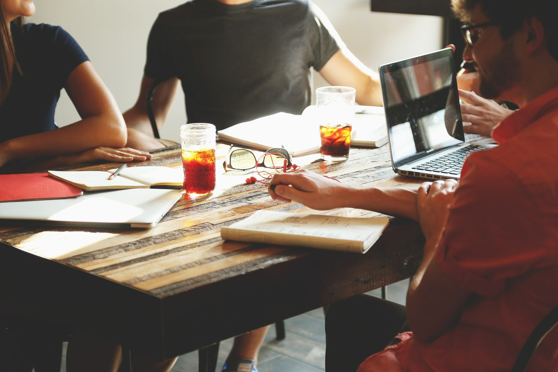 tres personas en una mesa con papeles y un ordenador para sacar la licencia de apertura