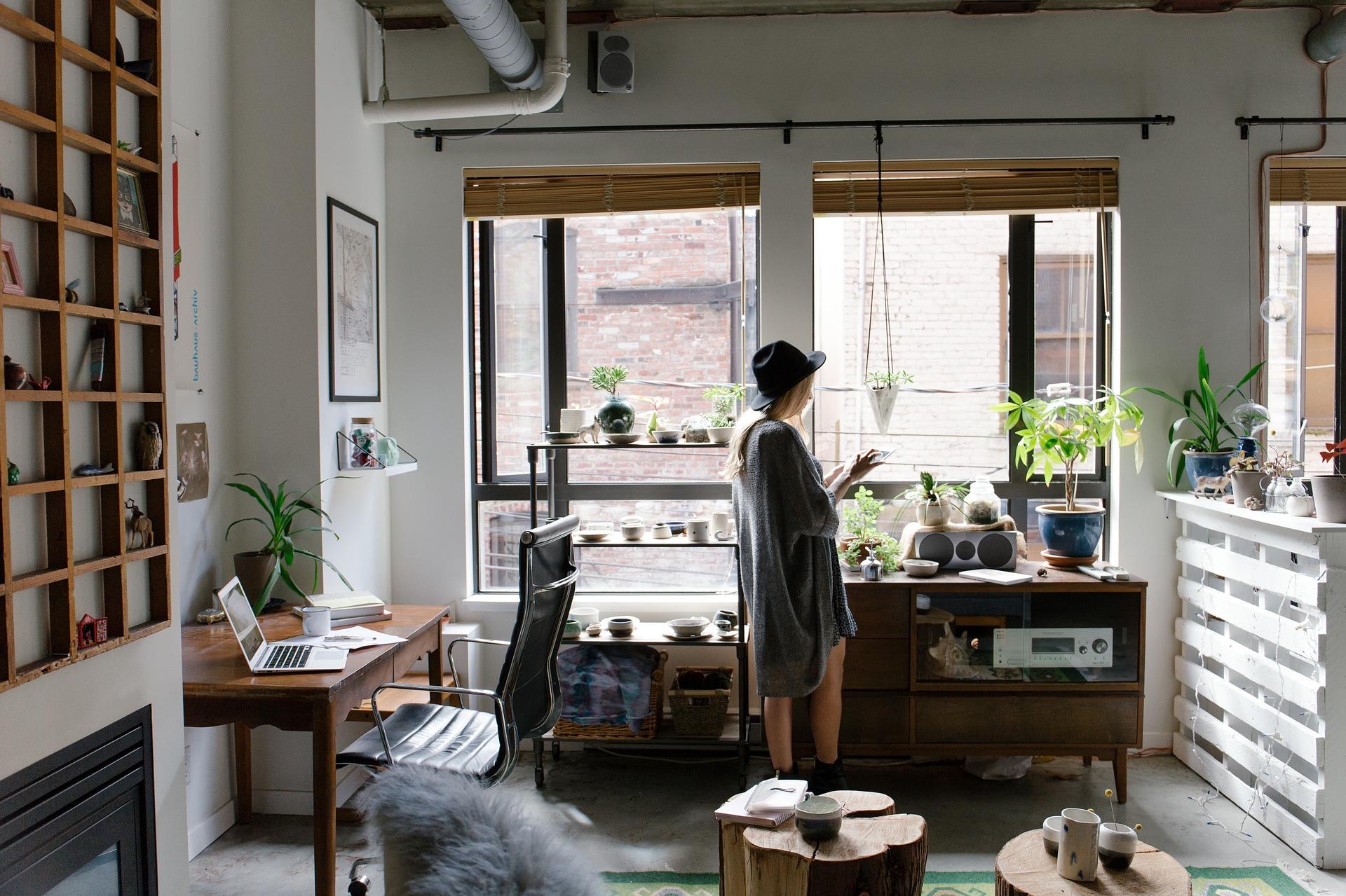 Una mujer en su salón mirando en el móvil cómo funciona el aplazamiento de deudas en la Seguridad Social
