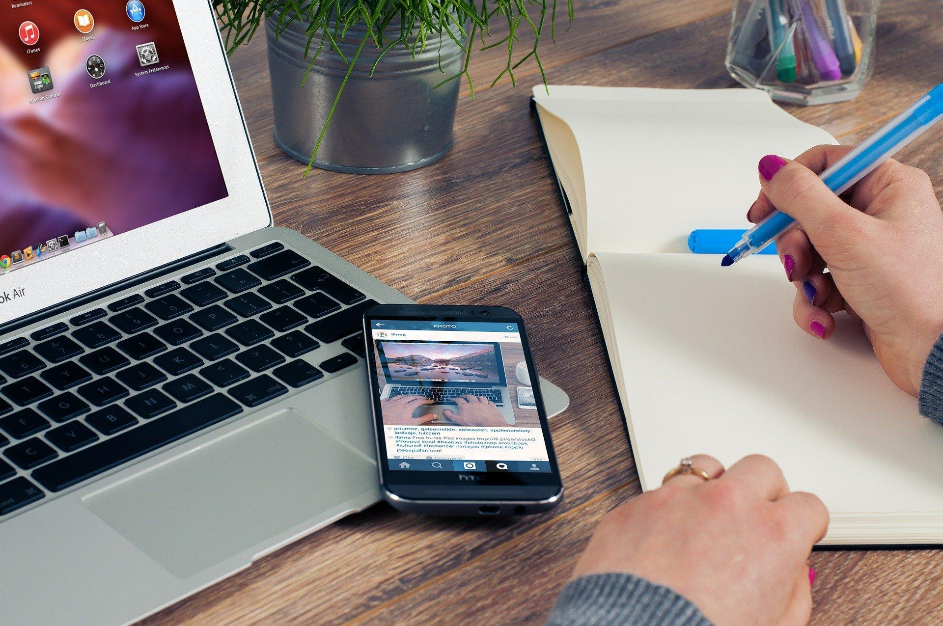 Un hombre escribiendo en una hoja la razón social de un autónomo con un móvil y un ordenador al lado