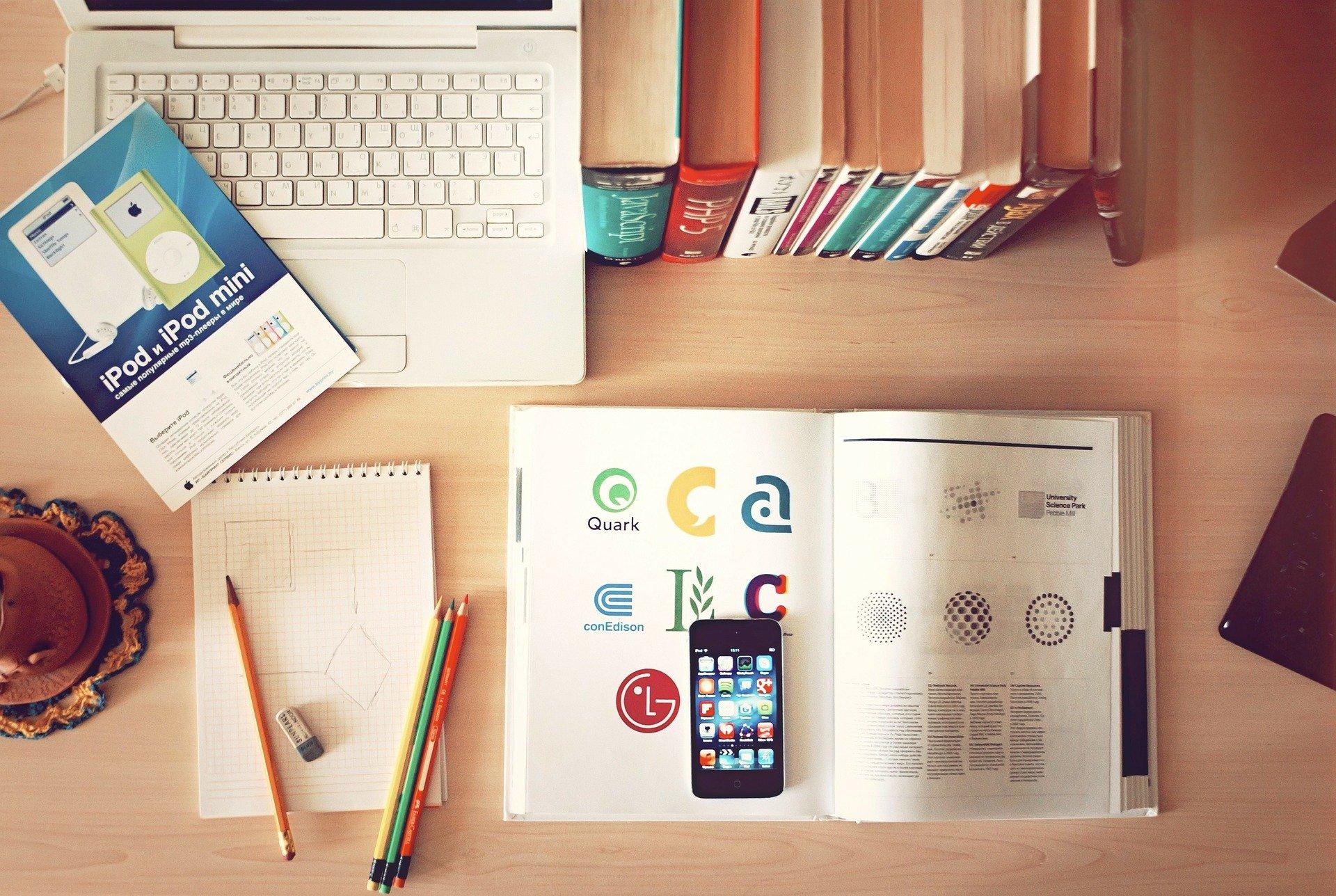 Una mesa con un móvil, libros, un ordenador y bolis para buscar información sobre el modelo 145