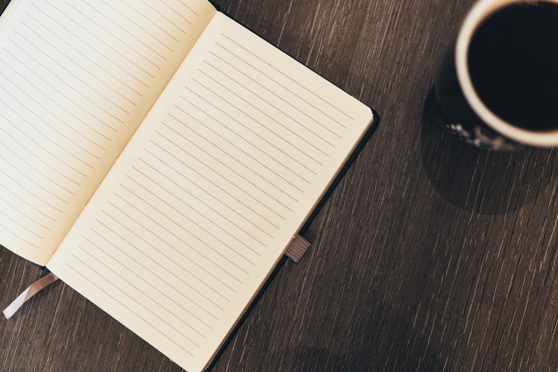una libreta y un café para buscar información sobre el paro de los autónomos