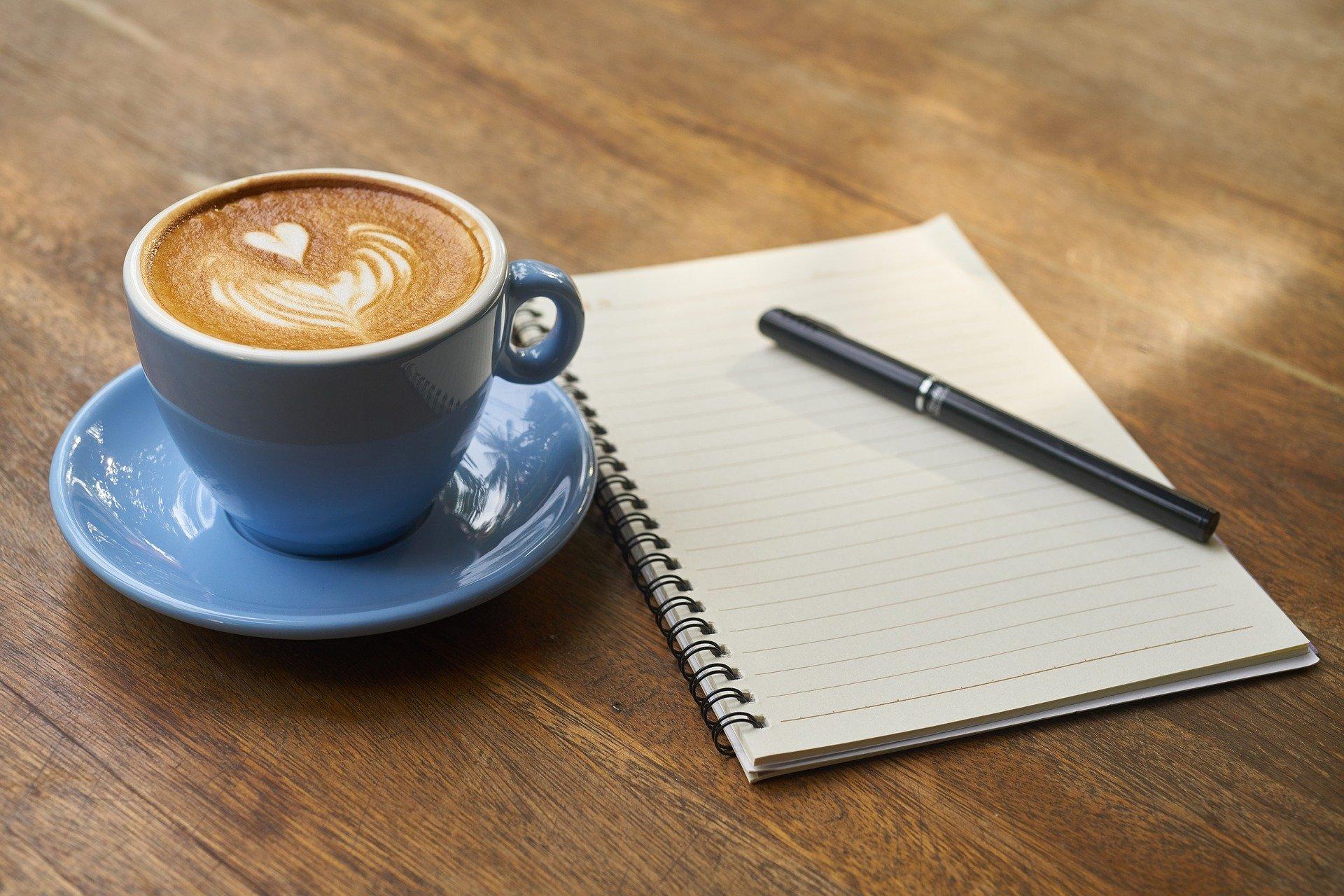 un café, una libreta y un boli para apuntar los tramos de IRPF del autónomo