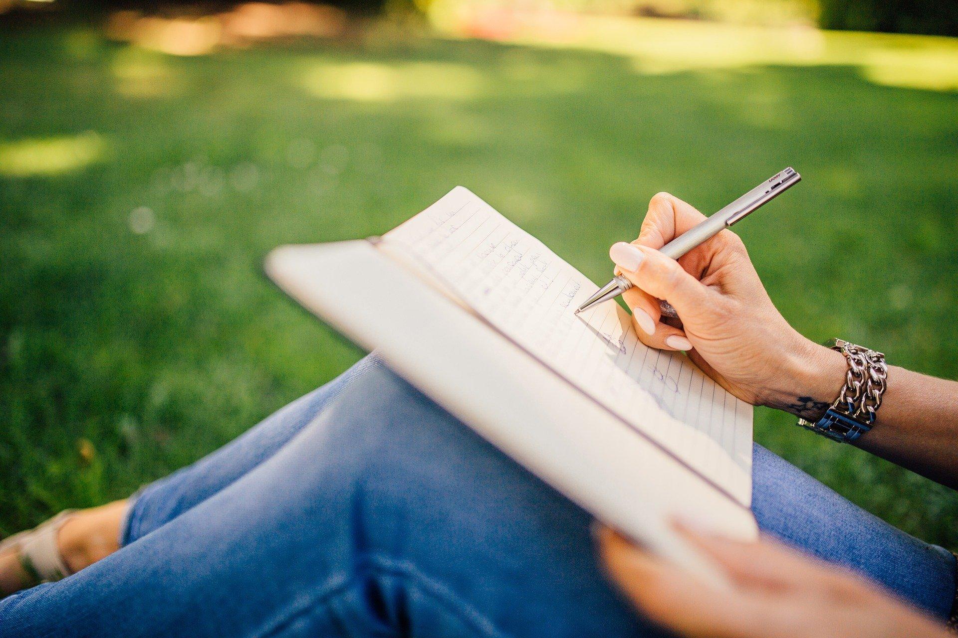 Las manos de una chica escribiendo en una libreta en el campo sobre el seguro de incapacidad temporal